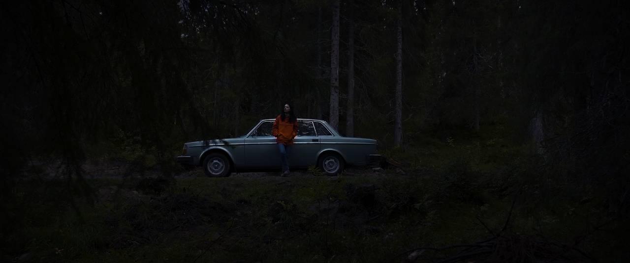 En kvinne står ved en bil, dypt inne i skogen.